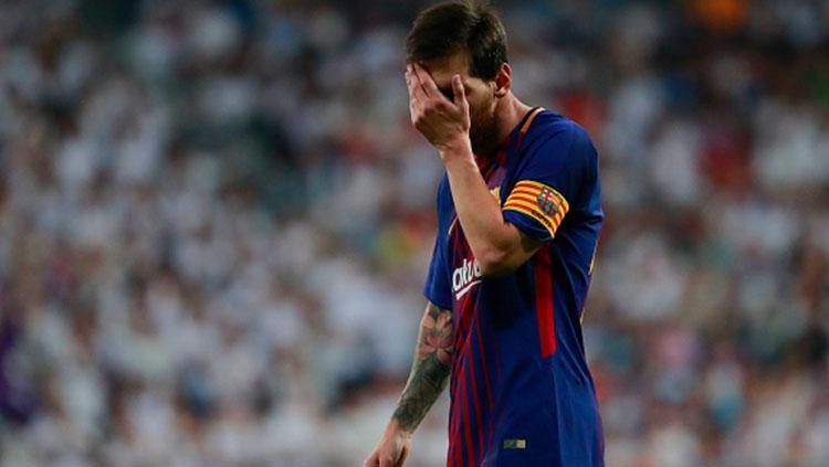 Lionel Messi menutup wajahnya usai Barcelona takluk dari Real Madrid. Copyright: INDOSPORT