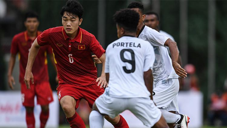 Pemain Timnas Vietnam, Luong Xuan Truong, berusaha melewati penjagaan penggawa Timor Leste. Copyright: Getty Images
