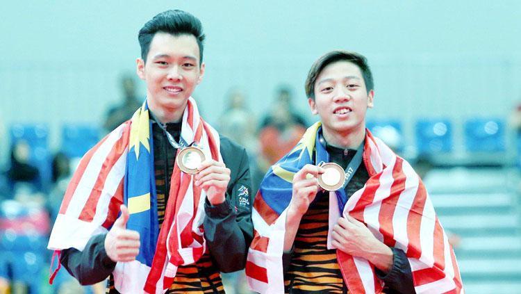 Jeremiah Loo Phay Xing (kanan) bersama Tan Fu Jie berjaya memenangi pingat emas dalam acara gimnastik artistik lelaki. Copyright: Twitter@bharianmy