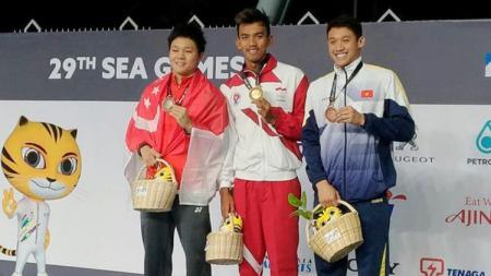 Triady Fauzi Sidiq (tengah) merebut medali emas 200 meter gaya ganti pada SEA Games 2017. - INDOSPORT