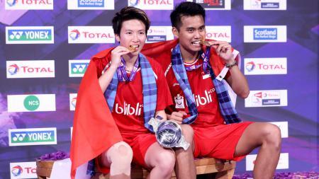 Tontowi/Liliyana menggigit medali emas pasca menjuarai Kejuaraan Dunia Bulutangkis 2017. - INDOSPORT