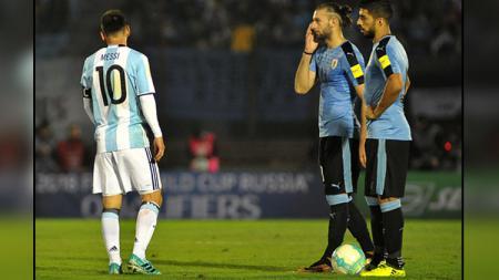 Lionel Messi (kiri/Argentina) dan dua pemain Timnas Uruguay, Gaston Silva (tengah), serta Luis Suarez. - INDOSPORT