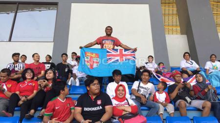 Suporter Timnas Fiji memegang bendera Fiji, hadir di Stadion Patriot. - INDOSPORT