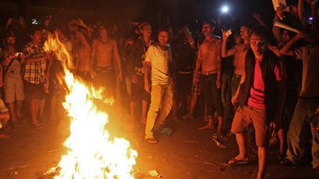 Suporter sepakbola Myanmar saat membakar pakaian di jalan dekat Stadion Thuwunna di Yangon. - INDOSPORT