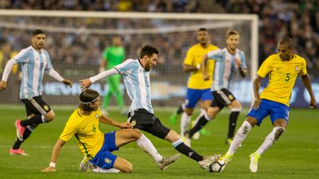 Lionel Messi tengah berusaha mengambil bola dari pemain Brasil. - INDOSPORT