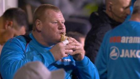 Wayne Shaw kala kedapatan makan sandwich di bangku cadangan. - INDOSPORT