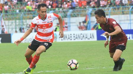 Pemain Madura United, Slamet Nurcahyo (kiri) berusaha melewati hadangan pemain lawan. - INDOSPORT