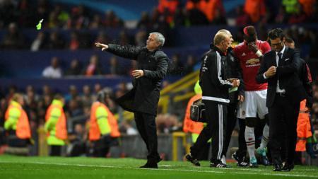 Paul Pogba (kanan merah) merintih kesakitan sambil berjalan meninggalkan lapangan, dengan Jose Mourinho di sebelahnya. - INDOSPORT