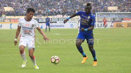 Pemain Bali United tampak fokus saat berhadapan dengan Ezechiel N'Douassel. - INDOSPORT