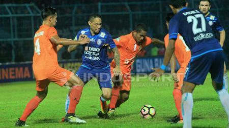 Mantan pemain Arema FC, Juan Pablo Pino dijaga ketat oleh Ryuji Utomo dan Pandi Lestaluhu. - INDOSPORT