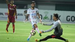 Indosport - Tendangan pemain Bali United, Stefano Lilipaly (tengah) digagalkan kiper Bhayangkara FC, Awan Setho (kanan).