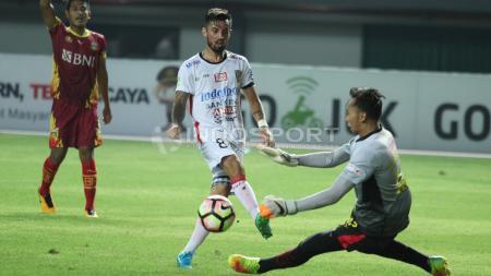 Tendangan pemain Bali United, Stefano Lilipaly (tengah) digagalkan kiper Bhayangkara FC, Awan Setho (kanan). - INDOSPORT