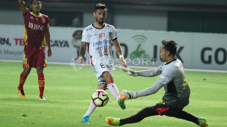 Tendangan pemain Bali United, Stefano Lilipaly (tengah) digagalkan kiper Bhayangkara FC, Awan Setho (kanan). Copyright: INDOSPORT/Herry Ibrahim