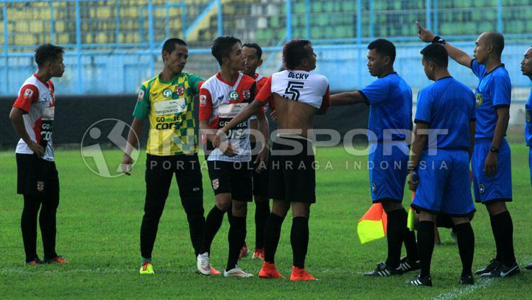 Aksi Deki Rolias Candra yang membuka baju dan diikuti sembilan pemain lainnya, sebagai protes kartu merahnya di menit 15. Copyright: Ian Setiawan/INDOSPORT