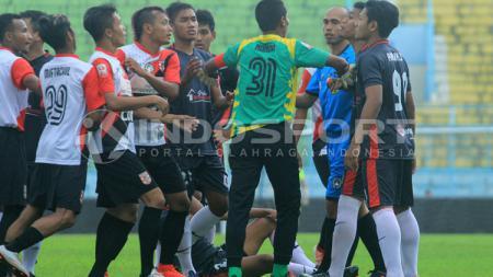 Wasit Suhardiyanto pun dibuat sibuk melerai pertengkaran pemain kedua tim sepanjang pertandingan. - INDOSPORT