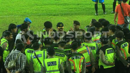 Ratusan polisi, merapatkan barisan untuk pengamanan pasca mengusir sejumlah penonton yang diduga provokator di tribun.