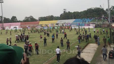 Polisi tengah mengamankan beberapa suporter yang ricuh dalam laga Persita Tangerang vs PSMS Medan. - INDOSPORT