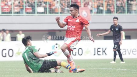 Aksi pemain Persija Jakarta, Abrizal Umanailo digagalkan kiper Persegres, Fitrul Dwi Rustapa. - INDOSPORT