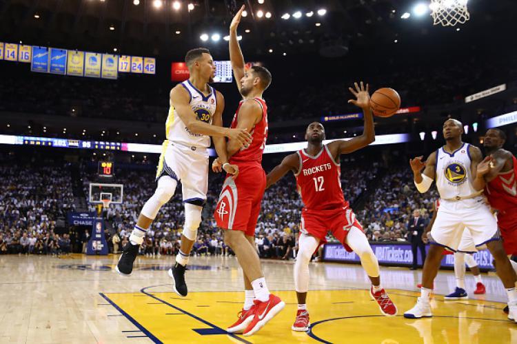Pemain megabintang Golden State Warriors, Stephen Curry (kiri) saat ingin memberikan umpan kepada rekannya, David West. Copyright: INDOSPORT