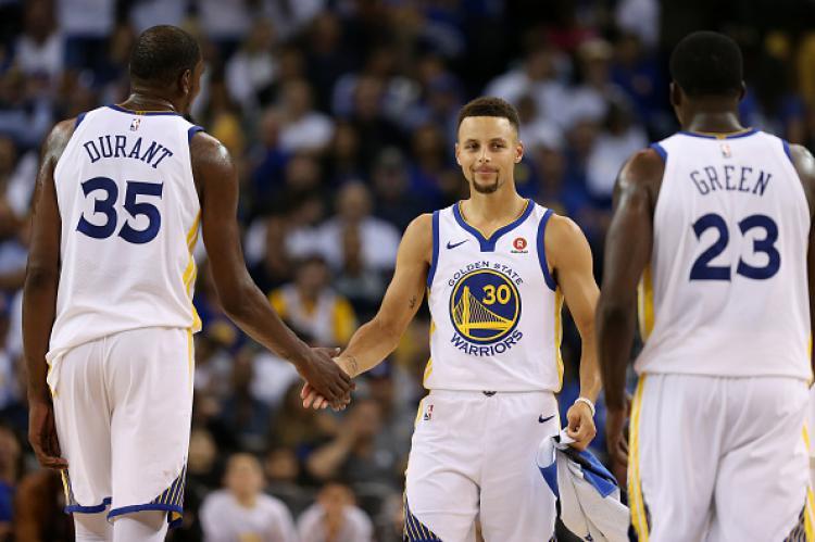 Pemain megabintang Warriors, Stephen Curry (tengah) mampu memberikan keunggulan untuk timnya di paruh babak pertama. Copyright: INDOSPORT