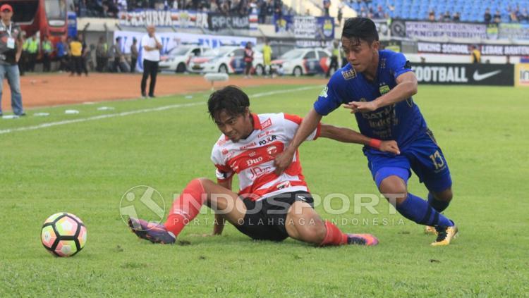 Pemain Madura United berusaha keras gagalkan aksi Febri Haryadi. Copyright: Arif Rahman/INDOSPORT