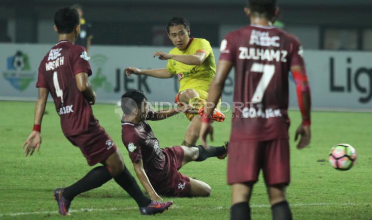 Pemain Bhayangkara FC, Lee Yujun (tengah) melakukan tendangaj ke gawang PSM Makassar. Copyright: Herry Ibrahim/INDOSPORT