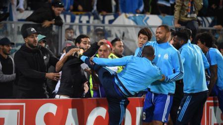 Patrice Evra melayangkan tendangan pada salah seorang fan. - INDOSPORT