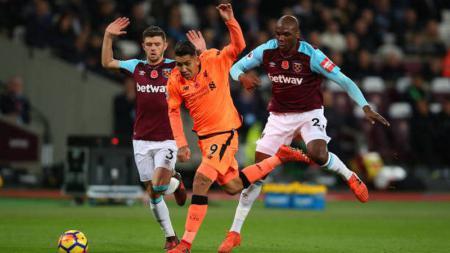 Roberto Firmino (tengah) berlari dari kawalan ketat pemain West Ham United. - INDOSPORT