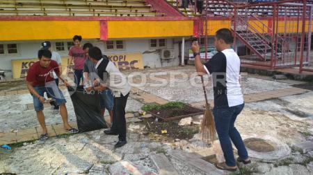 Sejumlah warga terlihat sedang membersihkan Stadion Andi Matalatta. - INDOSPORT