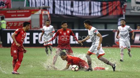 Salah satu pemain Persis Solo terjatuh saat menghalau pemain Martapura FC yang tengah menggiring bola. Herry Ibrahim/INDOSPORT - INDOSPORT