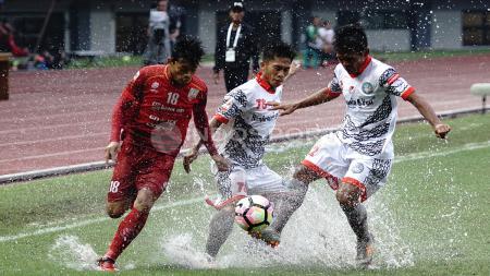 Pemain Persis Solo tengah menghadapi dua pemain Martapura FC untuk mendapatkan bola. - INDOSPORT