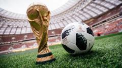 Indosport - Bola resmi Piala Dunia 2018, Telstar 18 bersama trofi Piala Dunia.