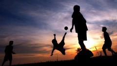 Indosport - Anak-anak Papua bermain bola di balik senja