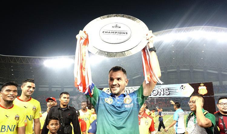Simon McMenemy mengangkat trofi juara Liga 1 2017. Copyright: Herry Ibrahim/INDOSPORT