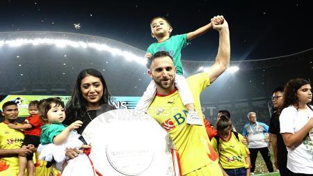Spasojevic bersama keluarga mengangkat trofi juara Liga 1 2017. - INDOSPORT