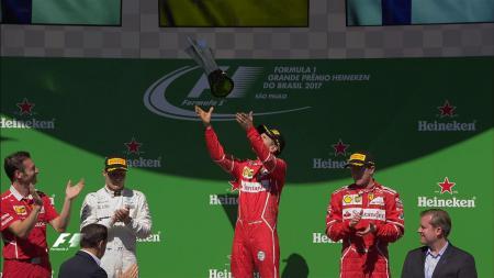 Sebastian Vettel melempar piala juara GP Brasil. - INDOSPORT