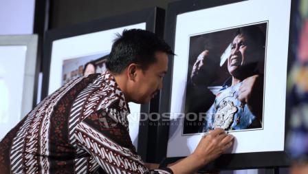 Menpora, Imam Nahrawi menandatangani salah satu foto dengan objek legenda tinju Indonesia, Elyas Pical. Herry Ibrahim/INDOSPORT