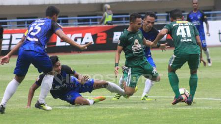 Pemain PSIS Semarang tampak melakukan penjegalan terhadap salah satu pemain Persebaya. - INDOSPORT