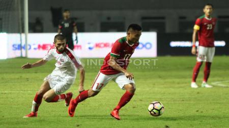 Saddil Ramdani berhasil melewati pemain Suriah dan membawa bola ke depan. Herry Ibrahim/INDOSPORT - INDOSPORT