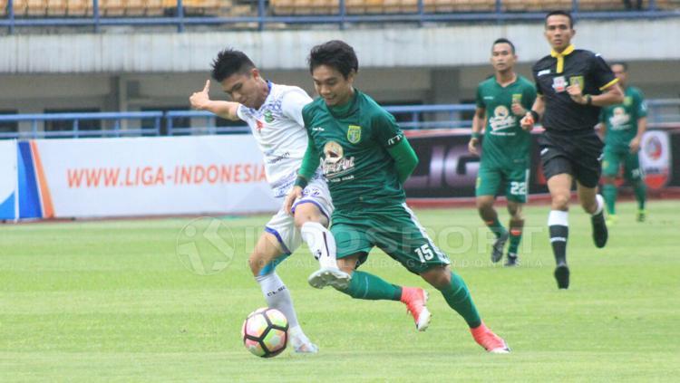 Pemain PSPS Riau tampak menjegal pemain Persebaya Surabaya. Copyright: Arif Rahman/INDOSPORT