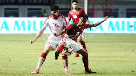 Muhammad Hargianto (kanan) tengah berusaha mengahalau pemain Suriah U-23. Herry Ibrahim/INDOSPORT - INDOSPORT