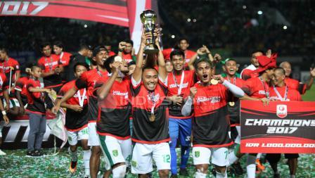 Kapten tim Persebaya, Rendi Irawan, penuh suka cita mengangkat trofi juara Liga 2 2017.