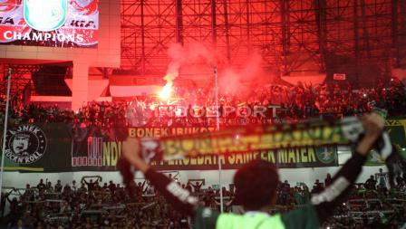 Suporter Persebaya menyalakan flare usai tim pujaan mereka memenangi laga final Liga 2.