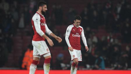 Mesut Ozil dan Olivier Giroud tertunduk lesu pasca menelan kekalahan dari Man United. - INDOSPORT