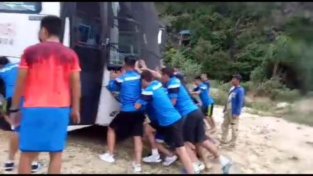 Para pemain Mongolia mendorong bus yang terjebak pasir di Pantai Lampuuk, Aceh, Rabu (6/12/17). - INDOSPORT