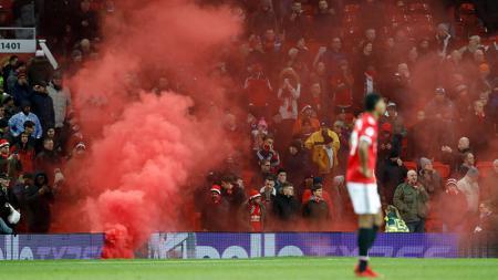 Flare yang dilemparkan oleh pendukung Manchester United. - INDOSPORT