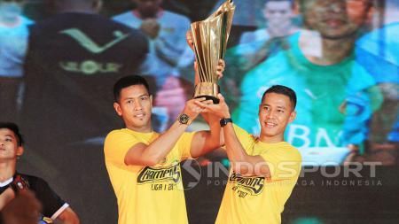 Indra Kahfi dan Jajang Mulyana tidak bisa menyembunyikan ekspresi bahagia saat mengangkat trofi juara Liga 1. - INDOSPORT