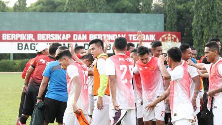 Para pemain PS TNI melakukan tos setelah melakukan latihan. - INDOSPORT