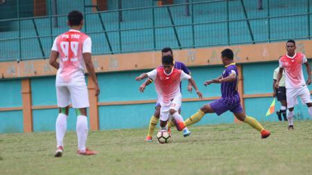 Pemain PS TNI mendapat perlawanan dari pemain UiTM FC. - INDOSPORT