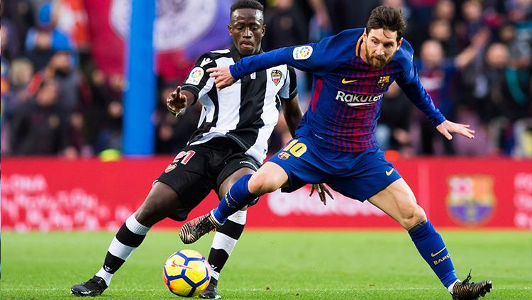 Lionel Messi berduel dengan salah satu pemain Levante. Copyright: INDOSPORT